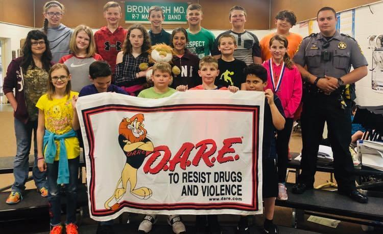 Group picture with the D.A.R.E class. The children in the front are holding a sign reading 'D.A.R.E to resist drugs and violence.'